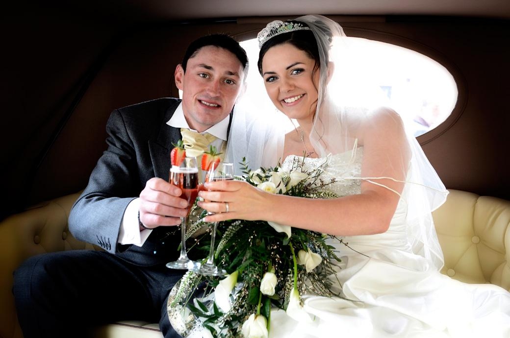 Happy newly-wed couple celebrate with champagne in this wedding photograph taken in the wedding car outside Addiscombe Catholic Church by wedding photographers in Surrey