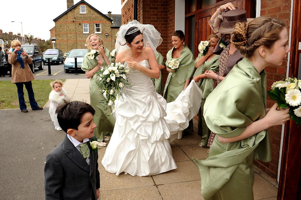 Bride and Bridesmaids dealing with the weather in this wind blown wedding picture captured at Surrey wedding venue Addiscombe Catholic Church Our Lady of the Annunciation