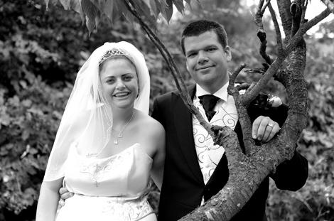 Happy and relaxed Bride and Groom by a tree wedding picture captured All Saints' Church Guildford a Surrey wedding venue with a pleasant field behind it