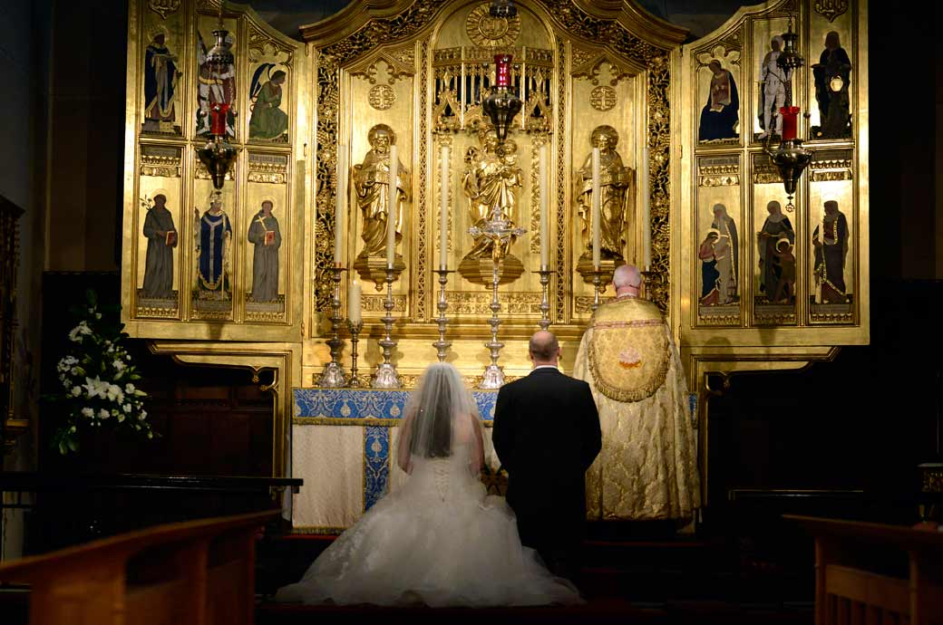 Bride and Groom wedding picture of them kneeling before the impressive golden chancel at All Saints Carshalton in Surrey