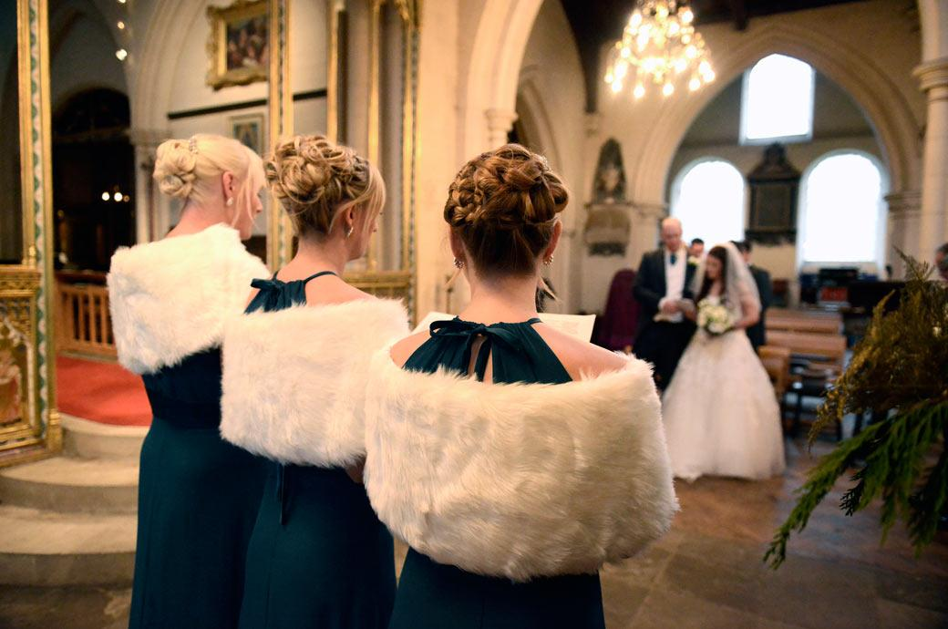Unusual and interesting back shot wedding photo of the Bridesmaids' white fur winter stoles captured at Surrey wedding venue All Saints Carshalton