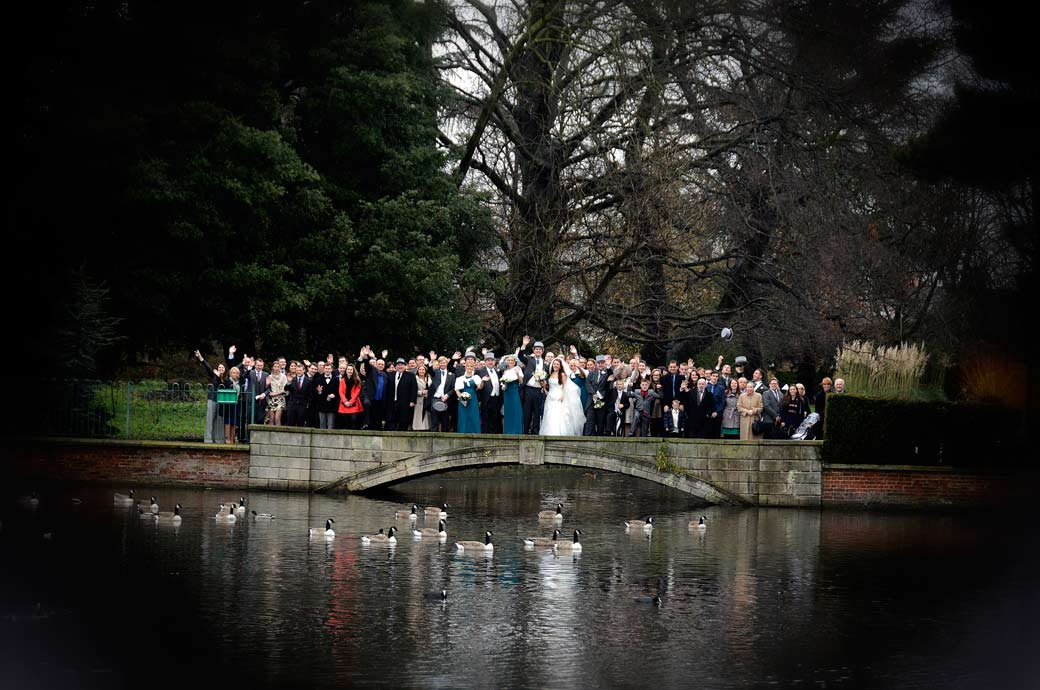 Atmospheric group wedding photograph of everyone waving from the bridge in Carshalton Ponds opposite All Saints Carshalton Church