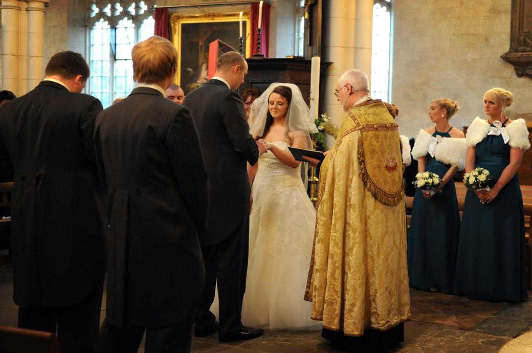 Groom placing the wedding ring on his excited Bride's finger taken at All Saints Carshalton Church an historic Surrey wedding venue