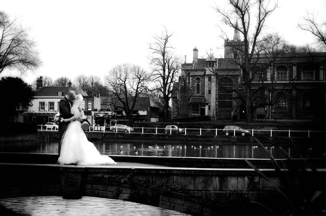 Romantic kiss on the bridge wedding photograph taken on the bridge in Carshalton ponds opposite All Saints Church Carshalton Surrey