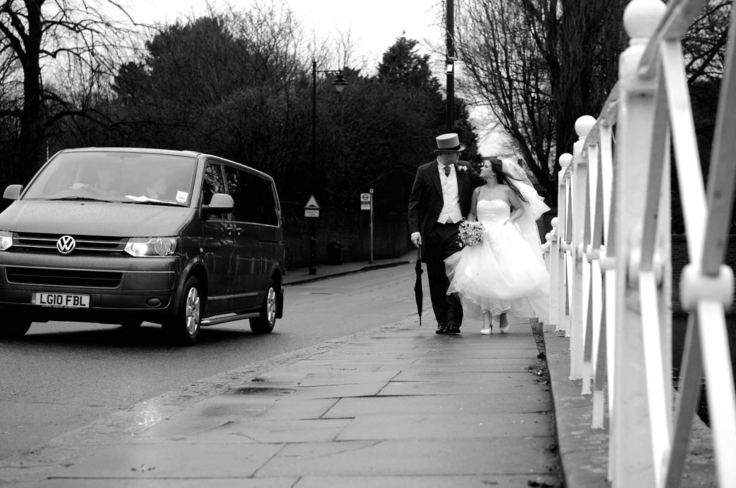 Atmospheric newly-weds wedding photo taken as they cross the bridge walking towards the Surrey wedding venue All Saints Carshalton