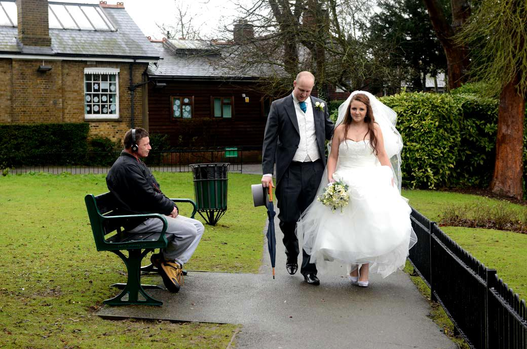 An unusual wedding photo of newly-weds walking past a man on a bench wearing his headphone captured opposite All Saints Carshalton in Surrey