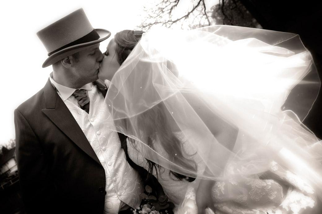 Romantic newly-weds black and white kissing photo captured on the bride in Carshalton Ponds opposite All Saints Carshalton in Surrey