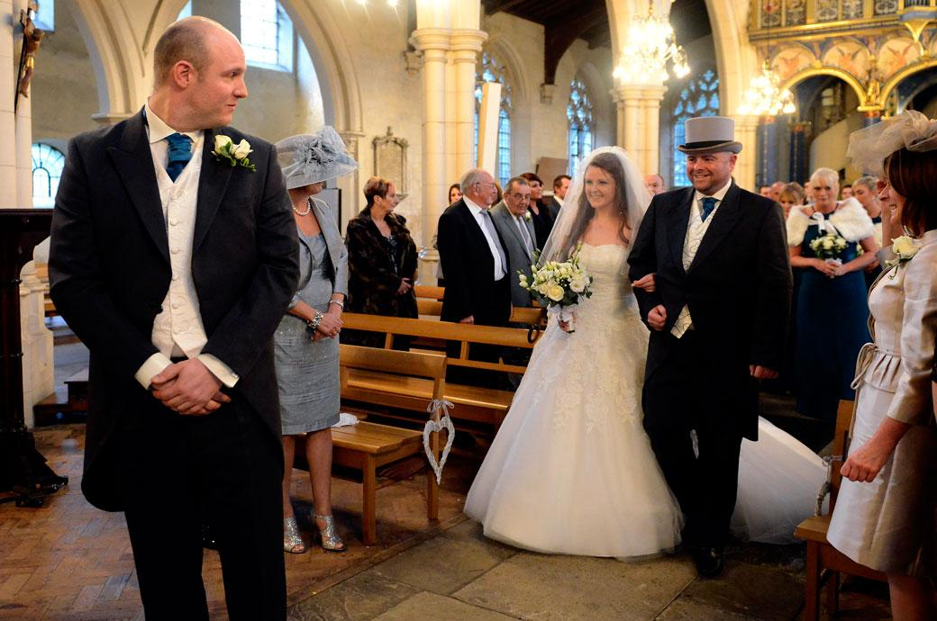A lovely moment captured of a smiling Bride as her eyes catch the Grooms down the aisle taken at All Saints Carshalton Surrey