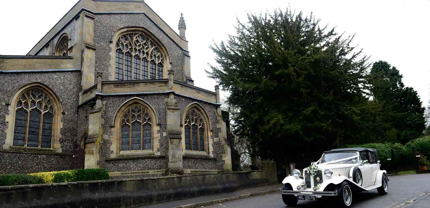 A pre-wedding photograph of the wedding car in front of the ancient and historic Surrey wedding venue that is  All Saints Church Carshalton