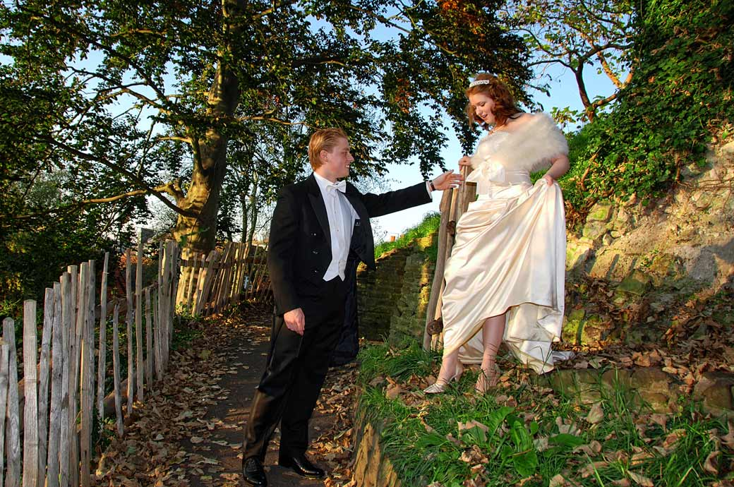 Groom in DJ helps his beautiful young wife onto the path in this wedding picture taken as they return to Surrey wedding venue The Angel Posting House, Guildford