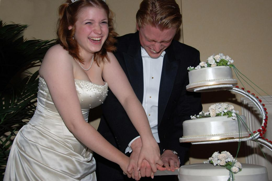 Extreme effort and laughter in this fun wedding photograph of the newly-weds at the Angel Posting House trying to cut into their wedding cake