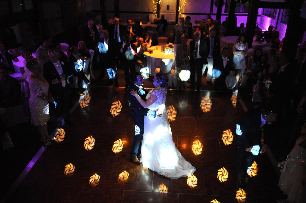 Bride and groom take their first dance captured in the colourful disco lights in this wedding photo taken in Surrey at the Burford Bridge Hotel from the Tithe Barn minstrel gallery