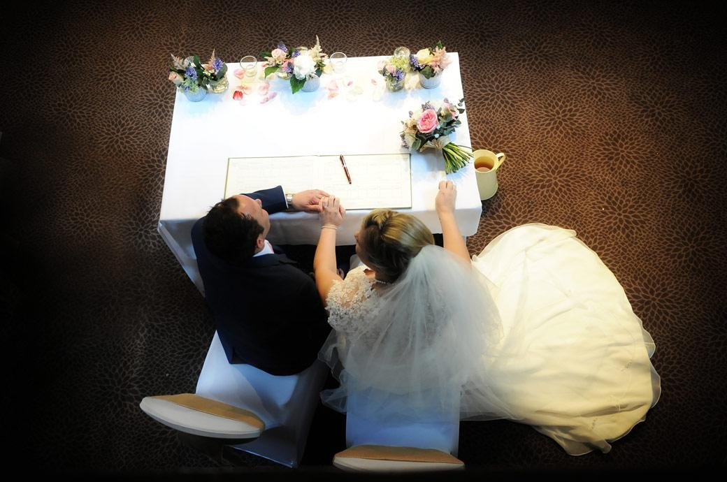 Aerial wedding photograph taken from the minstrel gallery in the Tithe Barn in the Burford Bridge Hotel Surrey of the newlyweds holding hands as they sit for photos