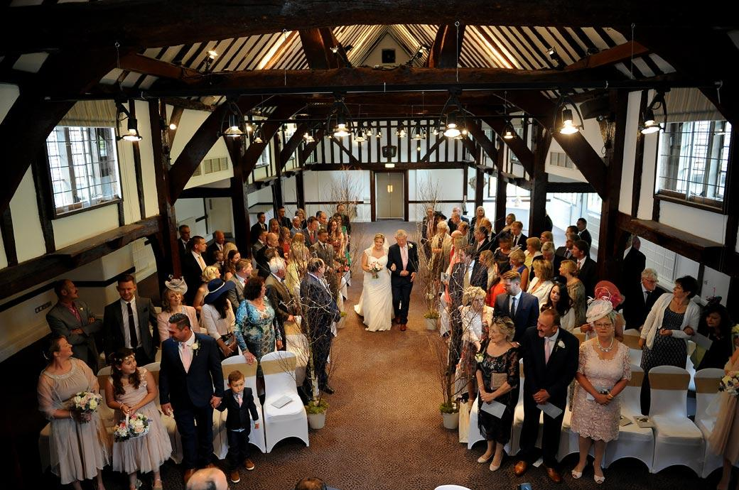 Bride walking down the aisle on her father's arm in this wedding photo taken in the ancient Tithe barn in Surrey wedding venue Burford Bridge Hotel from a balcony