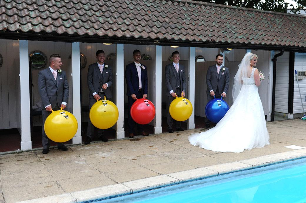 The smiling gents standing to attention at Burford Bridge Hotel Surrey in the swimming pool doorways with their Space Hoppers in hand as the bride walks past