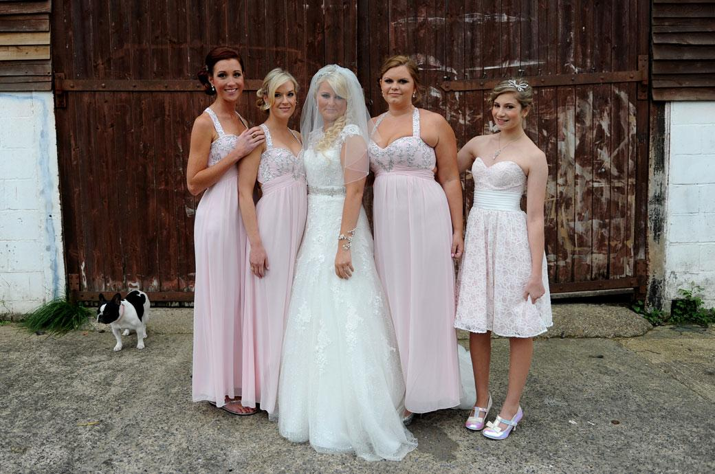 Bride poses with her Bridesmaids in this sweet wedding photograph taken before she leaves her parents home in Surrey for Burford Bridge Hotel in Dorking