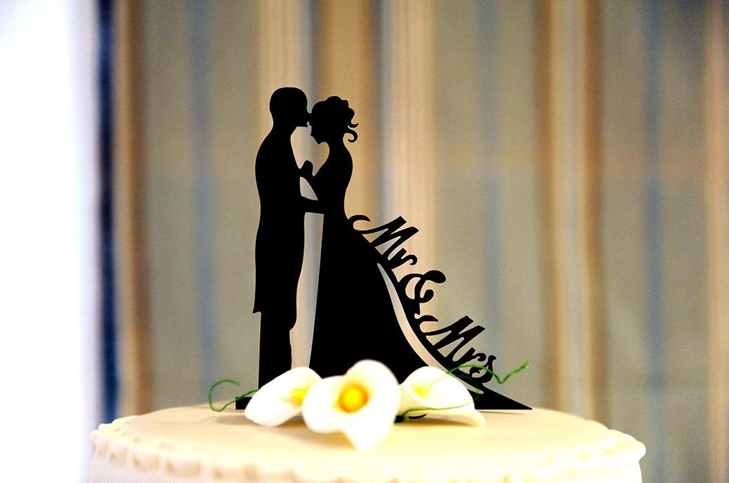 Delicate but striking silhouette cake topper captured at popular wedding venue Burford Bridge Hotel in the Tithe Barn Surrey