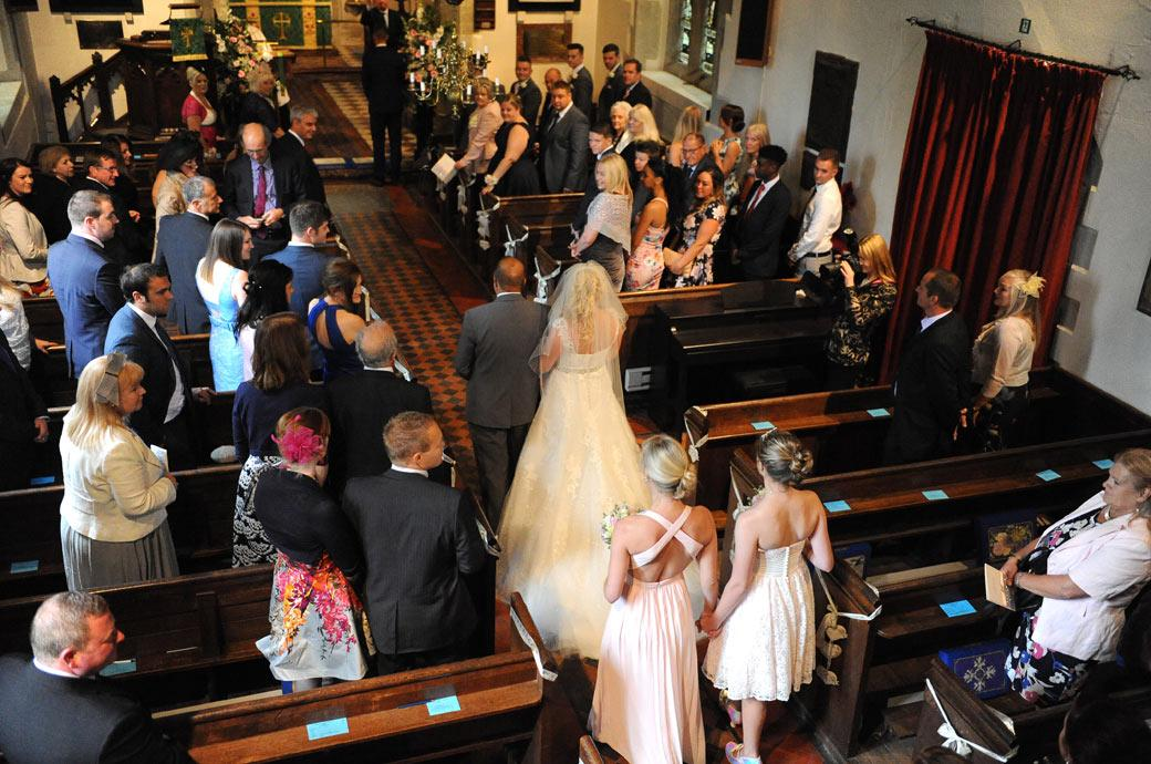 Aerial wedding photo taken from the choir balcony of the Bride walking down the aisle for her Surrey church wedding followed by a reception at Burford Bridge Hotel in Dorking