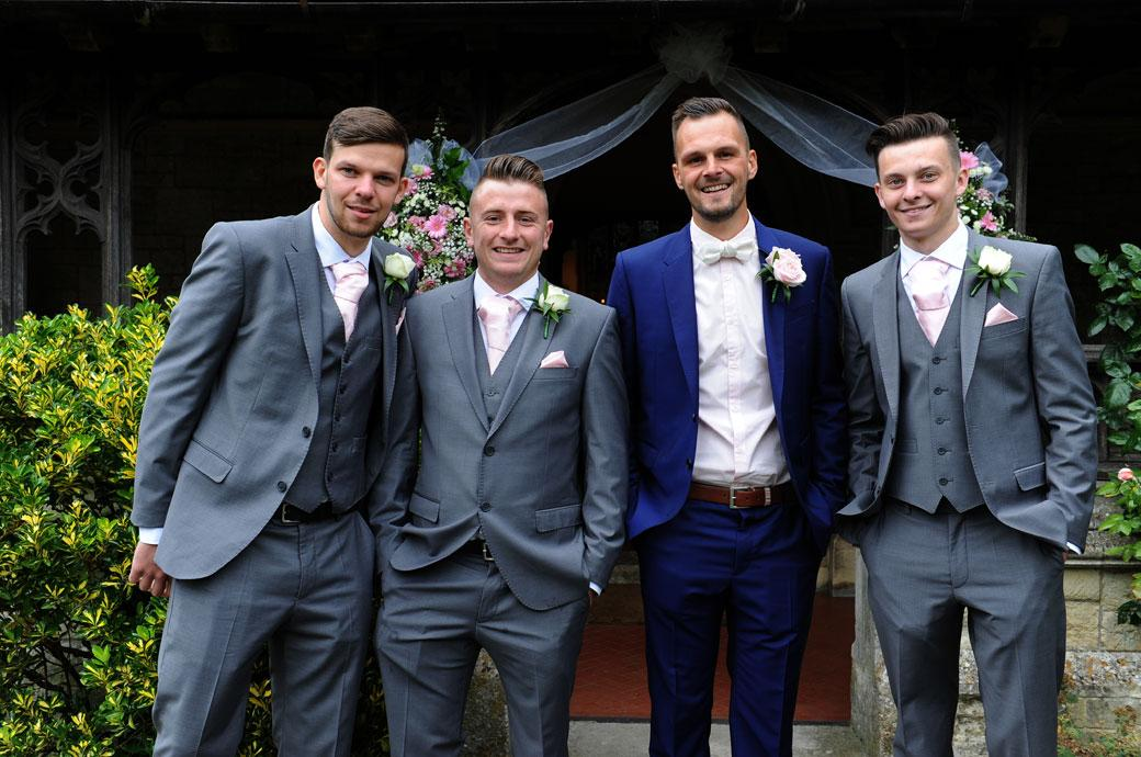 Smiling Groom with his groomsmen as they stand outside the church awaiting guests followed by a reception at Surrey wedding venue Burford Bridge Hotel