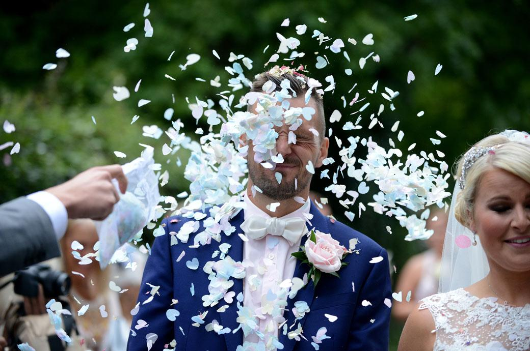 Funny wedding photo of the Groom getting swamped with wedding confetti outside the church before leaving for the Burford Bridge Hotel Surrey wedding venue