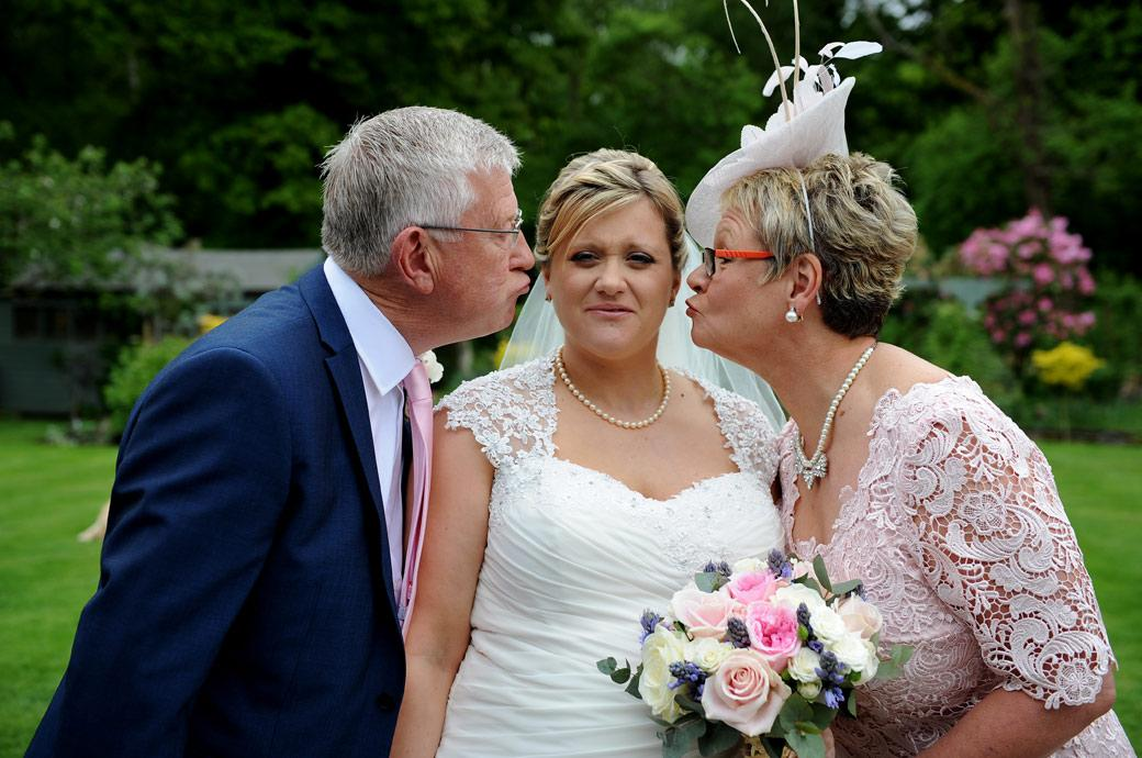 Bride pulls a face as her mum and dad try to kiss her in this fun wedding photo captured by a Surrey Lane wedding photographer before leaving for the Burford Bridge Hotel