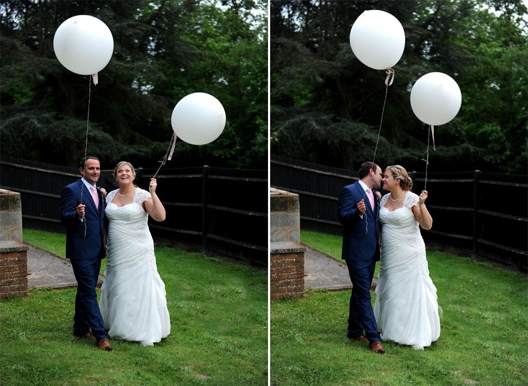 Wedding pictures of the Bride and Groom with white balloons taking a walk and having a kiss in the garden at the Burford Bridge Hotel in Surrey Dorking next to Box Hill