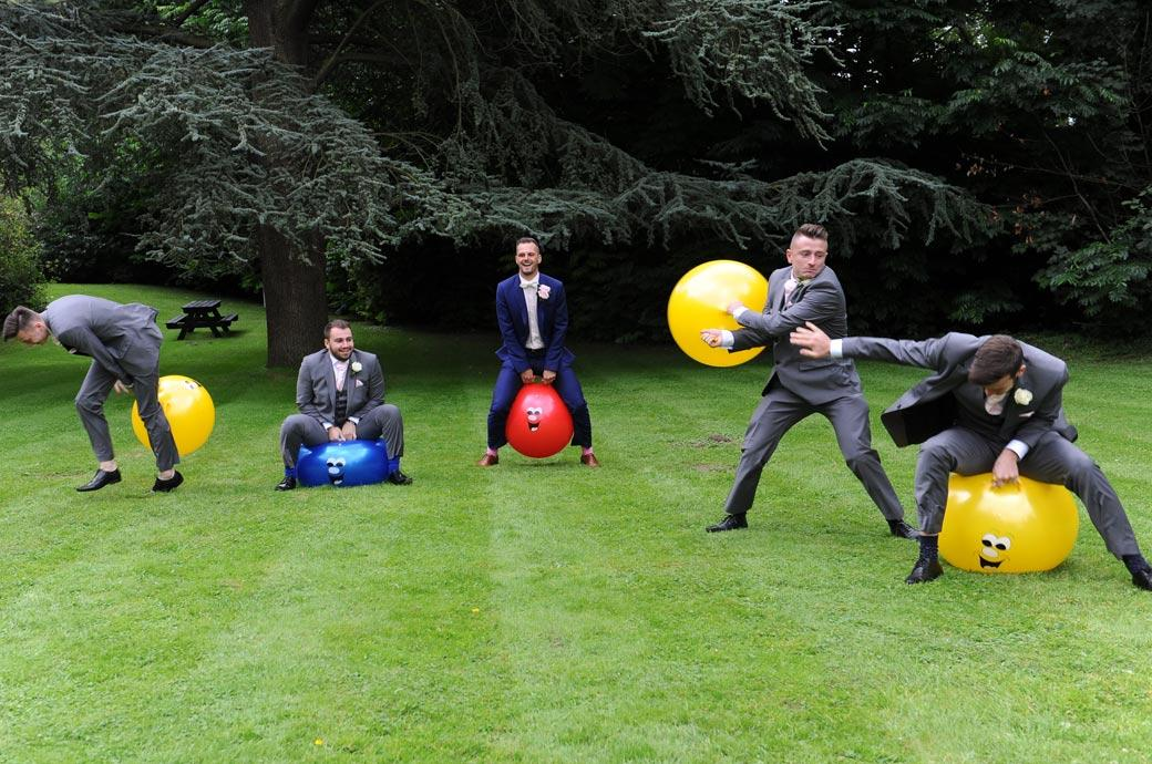 Groom and Groomsmen in this wedding picture having a race across the lawn at Surrey wedding venue Burford Bridge Hotel on different coloured space hoppers