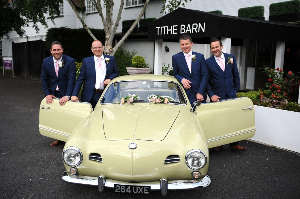 The Groom with his best me pose with a beautiful classic car outside the Tithe Barn at the Burford Bridge Hotel a fabulous wedding venue near Box Hill Surrey