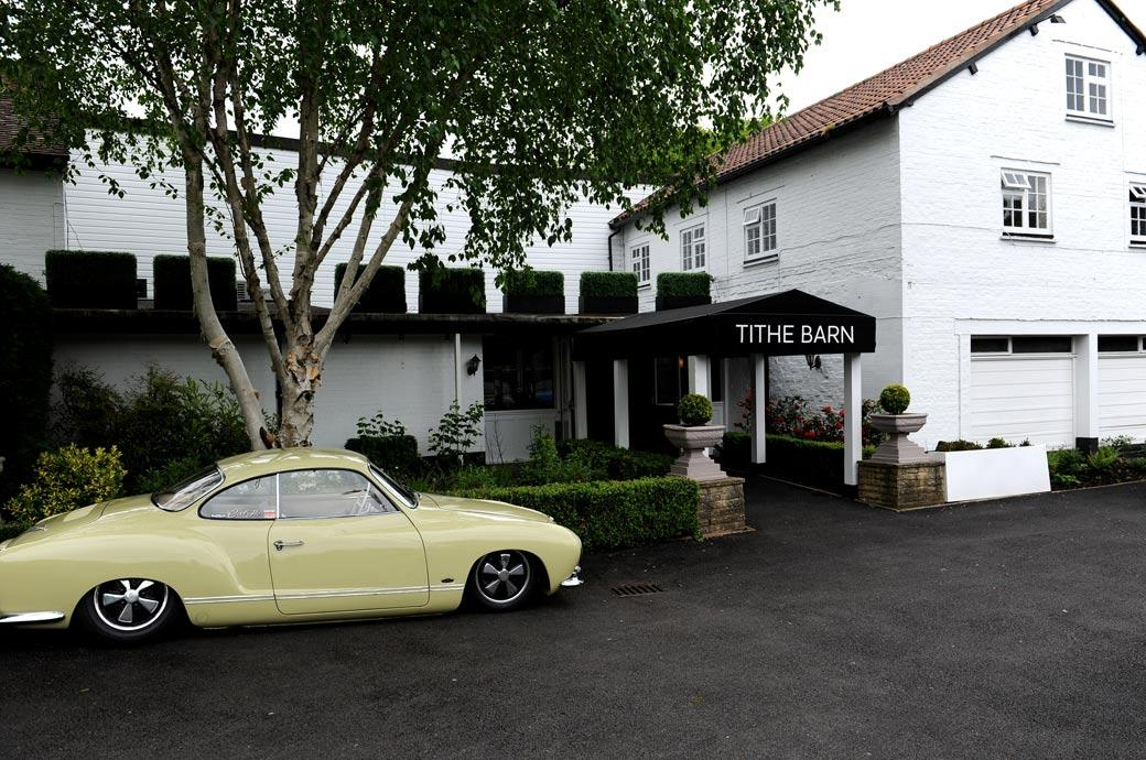 A cool classic wedding car awaiting the Bride and Groom in this wedding photograph taken outside Surrey wedding venue The Tithe Barn at the Burford Bridge Hotel