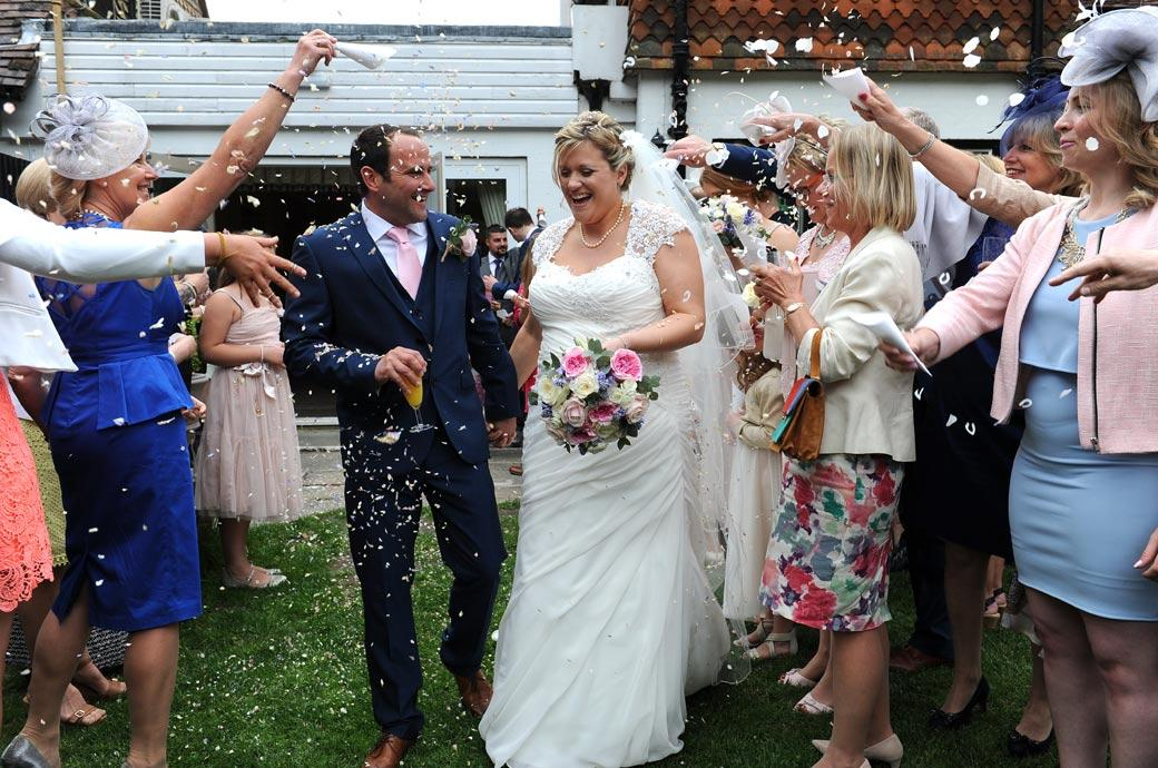 Time for confetti in this fun wedding picture captured of the newlyweds as they get covered at the Burford Bridge Hotel  wedding venue in Dorking near Box Hill
