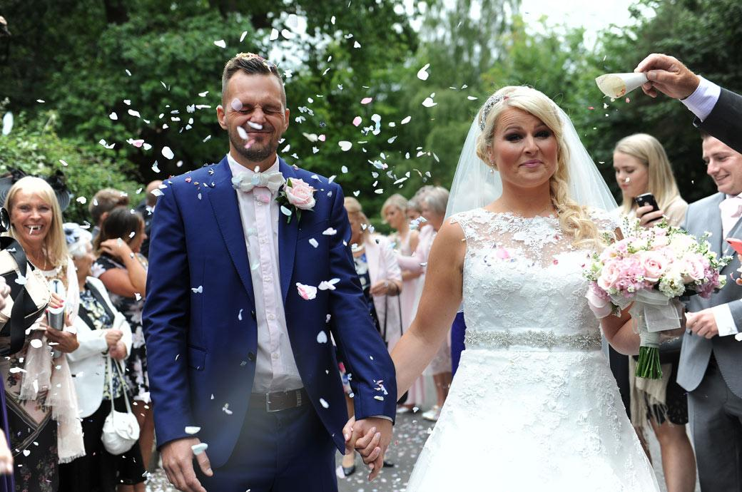 Bride and groom endure the confetti throwing in this fun wedding picture taken outside the church before leaving for Burford Bridge Hotel a popular wedding venue in Surrey