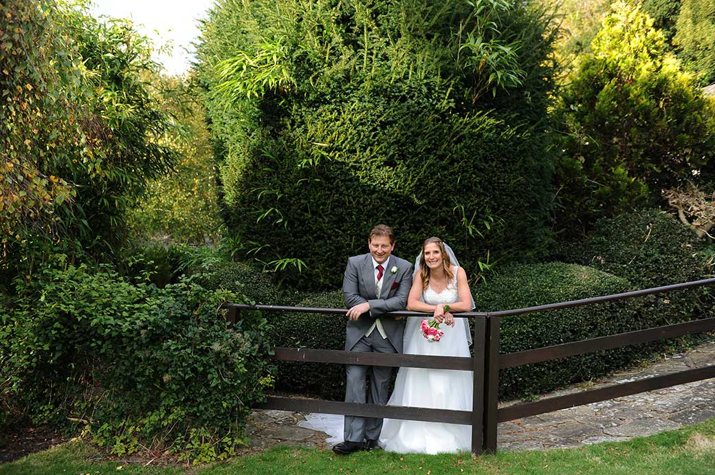 A Burford Bridge Hotel newlywed couple take time to relax as they lean on a fence in the tranquil gardens of this popular Surrey wedding venue
