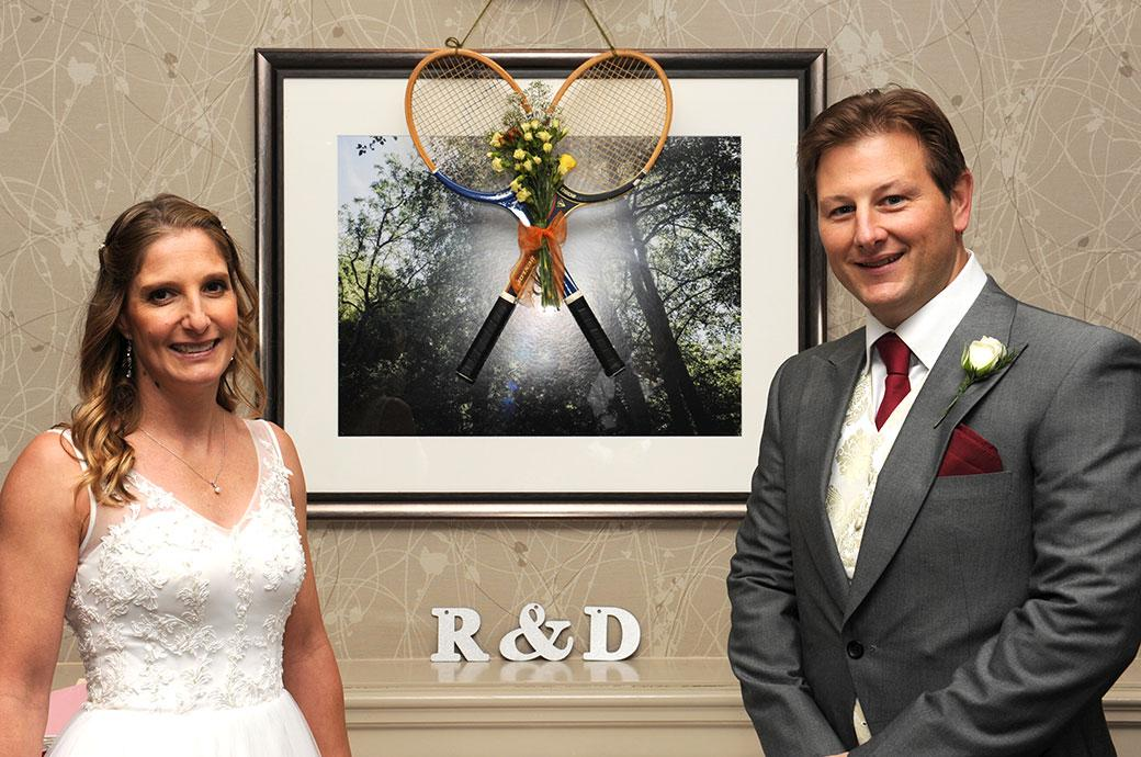 Bride and groom standing before their symbolic tennis rackets captured before they enter the Tithe Barn at Surrey wedding venue Burford Bridge Hotel in Dorking