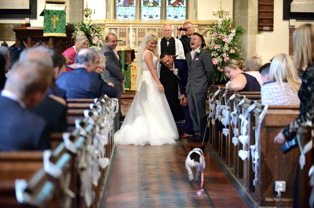 Wonderful wedding picture of everyone laughing as the Bride and Groom's dog comes down the aisle with the wedding rings before their Burford Bridge Hotel reception