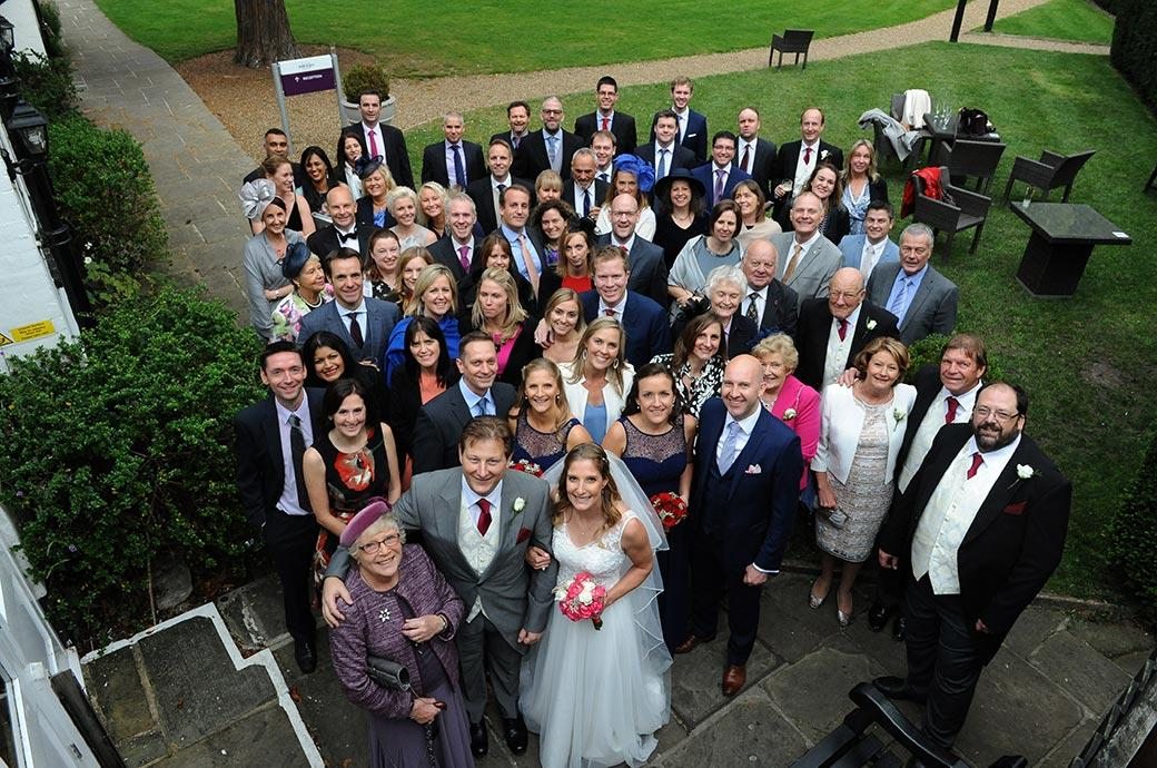 Everyone at the Burford Bridge Hotel wedding venue in Dorking Surrey captured outside the Tithe Barn looking up to the photographer on the fire escape