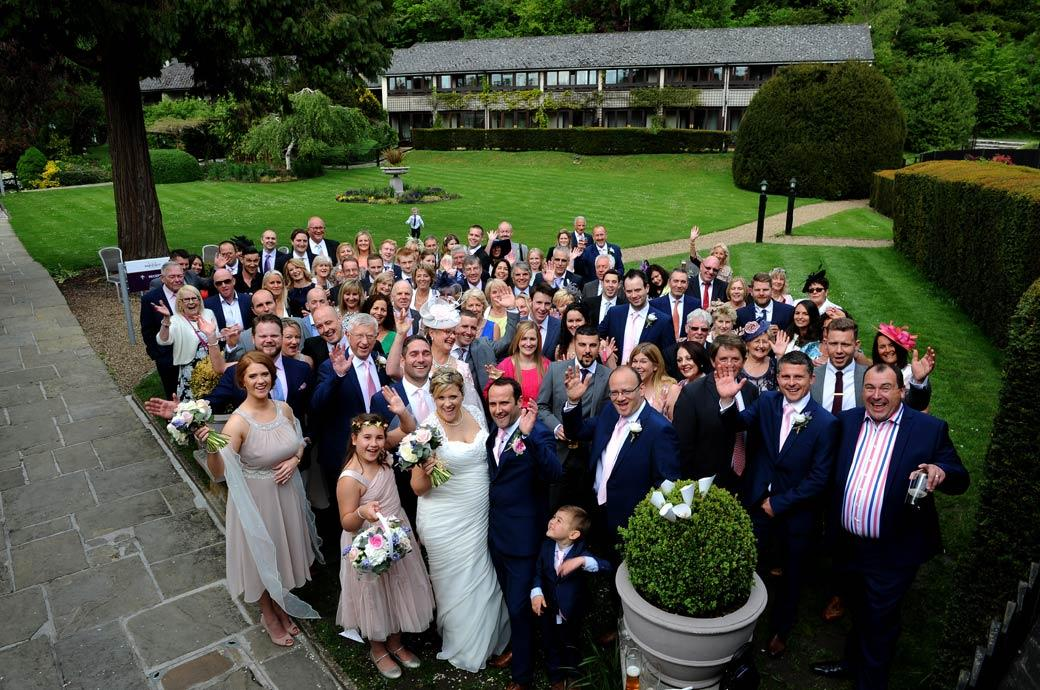 Aerial wedding photograph of everyone at a Burford Bridge Hotel reception waving up at the Surrey Lane wedding photographer up on the iron stairs