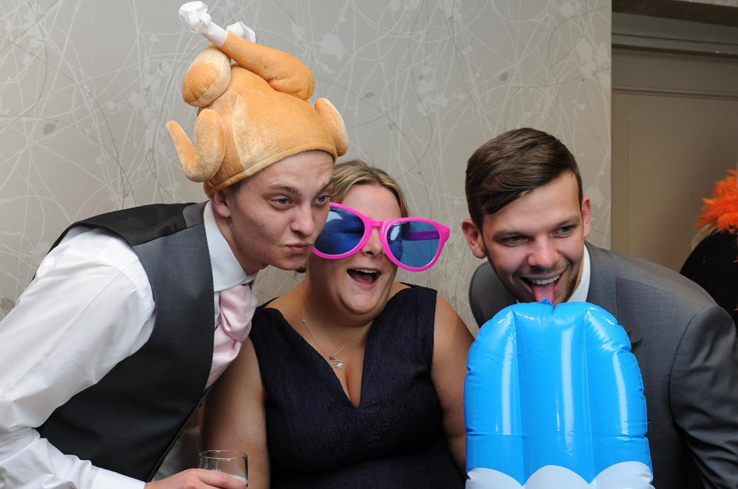Wedding guests enjoying dressing up for the fancy dress photo booth in this Burford Bridge Hotel wedding picture captured in Dorking Surrey