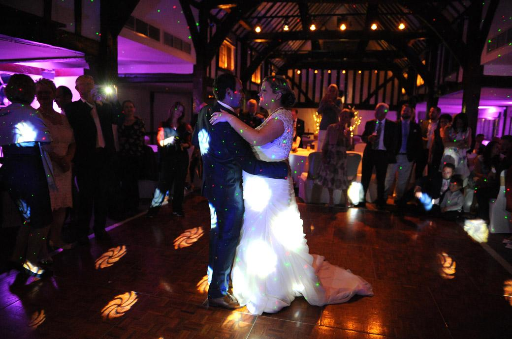 A smiling Bride enjoys her first dance in this atmospheric wedding picture from the Burford Bridge Hotel in Surrey complete with red and green spots of disco lights