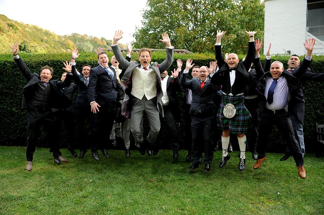 Fun group wedding picture taken in the garden of Surrey venue Burford Bridge Hotel in Dorking of the groom with the gents all jumping into the air