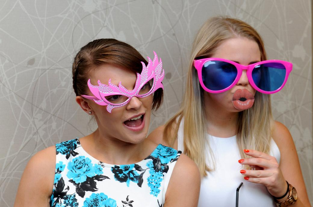 Fun and colourful wedding picture of ladies with fancy dress glasses on ready for the photo booth in Surrey at Burford Bridge Hotel in Dorking