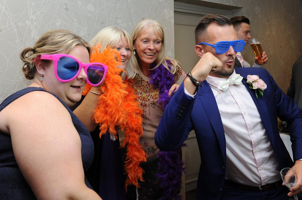 The Groom gets into his stride with orange glasses on as he poses for a photo booth picture at Burford Bridge Hotel captured by Surrey Lane wedding photographers