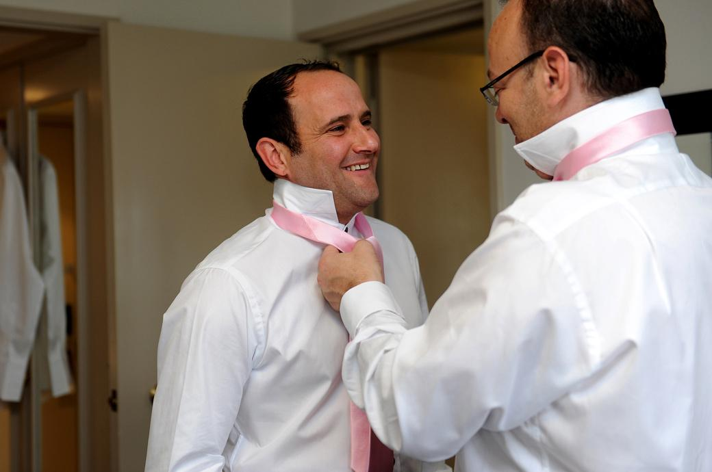 Smiling Groom having a helping hand from his Best man with his tie as he prepares to get married at the Burford Bridge Hotel captured by a Surrey Lane wedding photographer