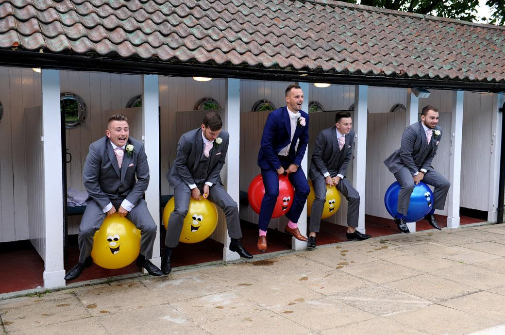 Groom leads the way as he leaps out of a swimming pool changing cubicle at Burford Bridge Hotel in Dorking Surrey on a different Space Hopper