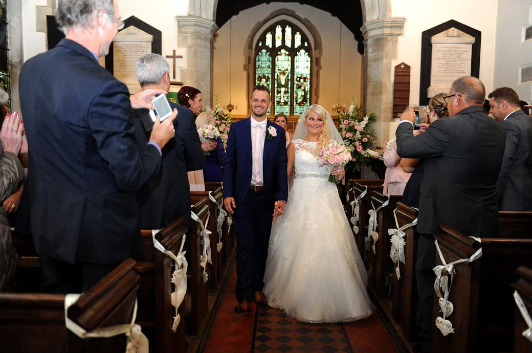 Smiling Bride and Groom walk captured in this wedding photograph walking down the aisle after getting married ready to go for their reception at Burford Bridge Hotel
