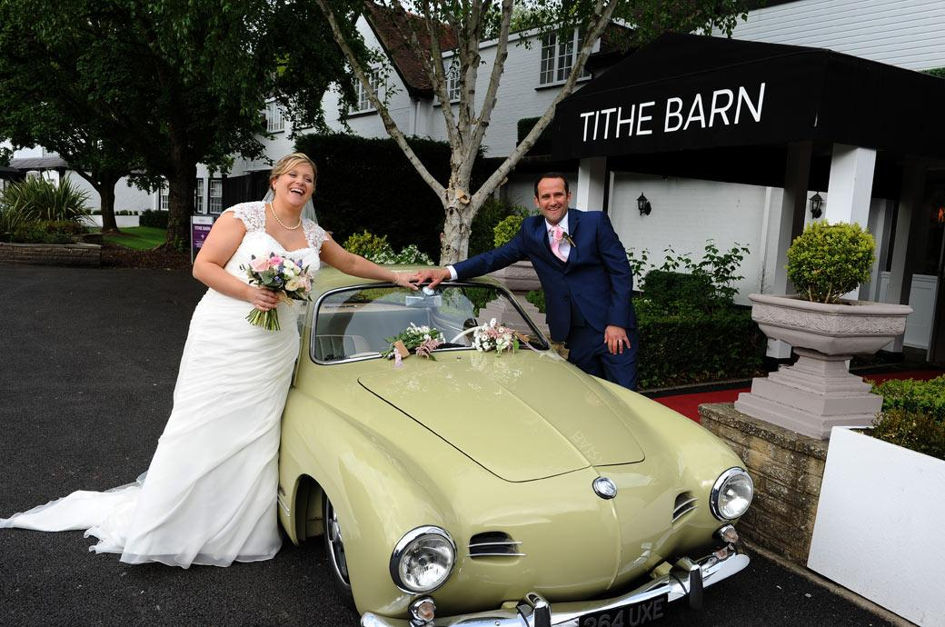 Bride and groom hold hands over a beautiful classic car in this happy wedding photograph taken in Surrey at the Burford Bridge Hotel Dorking outside the Tithe Barn