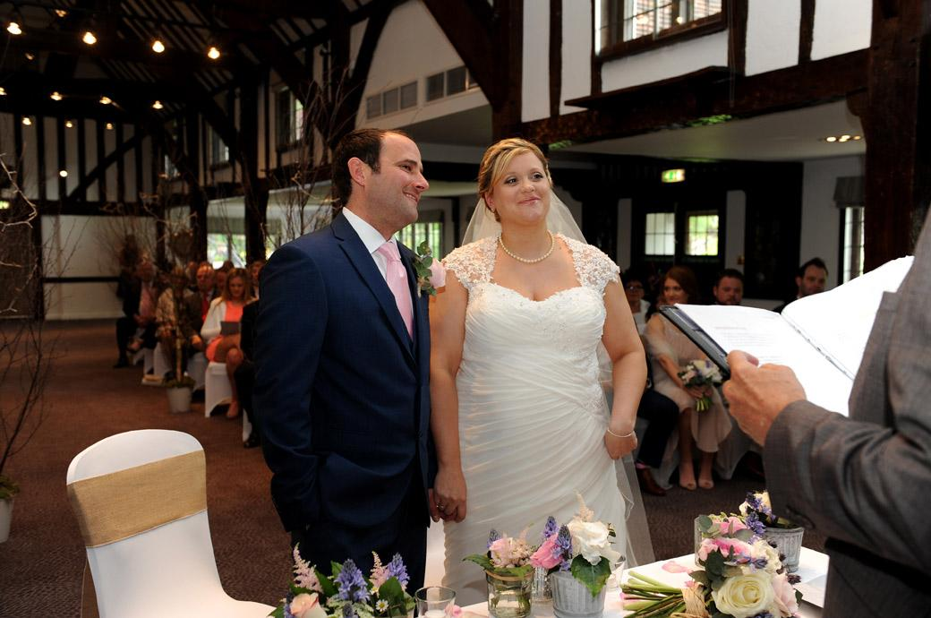 Wedding picture of a very happy smiling couple standing before the Registrar as they are announced husband and wife in the Tithe Barn at Burford Bridge Hotel Surrey