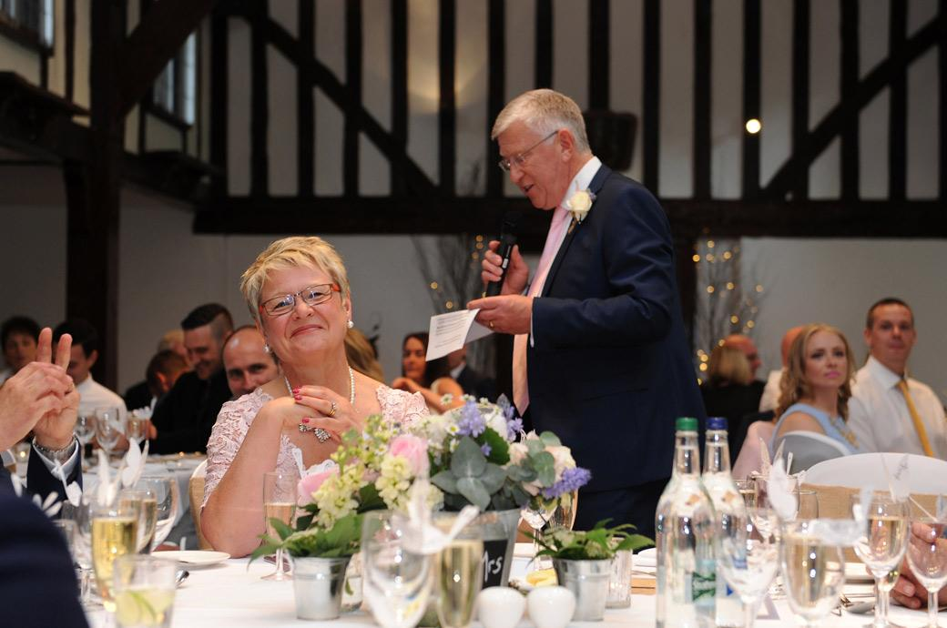 Father of the Bride makes the Mother of the Bride laugh during the wedding speeches captured Dorking Surrey in the Tithe Barn at the Burford Bridge Hotel