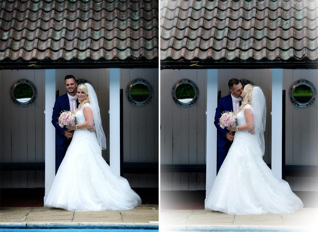 Newlyweds posing and kissing in front of the open air swimming pool changing cubicles captured in these wedding picture from Burford Bridge Hotel Surrey