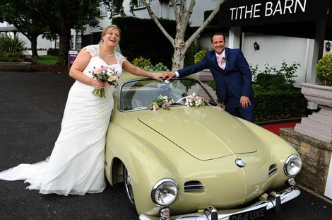 Newlywed couple in this Surrey wedding photo taken as they hold hands over their lovely classic wedding car parked outside the Tithe Barn at Burford Bridge Hotel Dorking