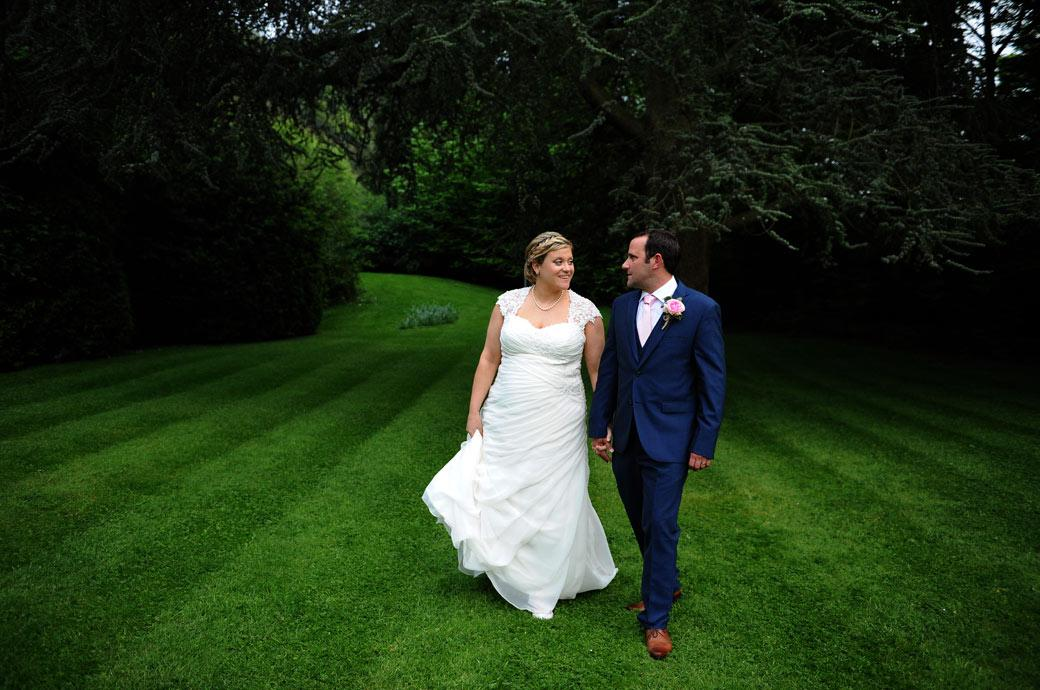 Newlyweds hold each other's gaze as they take a romantic walk on the lawn away from the reception celebrations in Dorking Surrey at the Burford Bridge Hotel